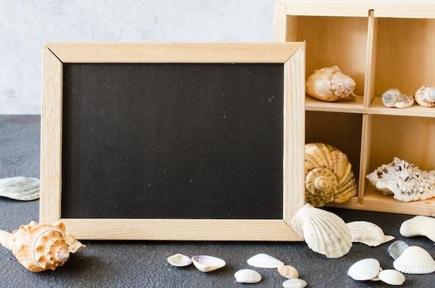 Empty chalkboard or photo frame with seashells.