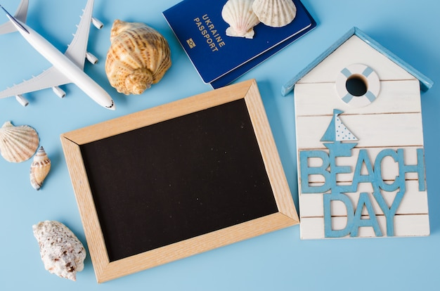 Empty chalkboard with decorative airplane, passports and seashells . summer travel concept.
