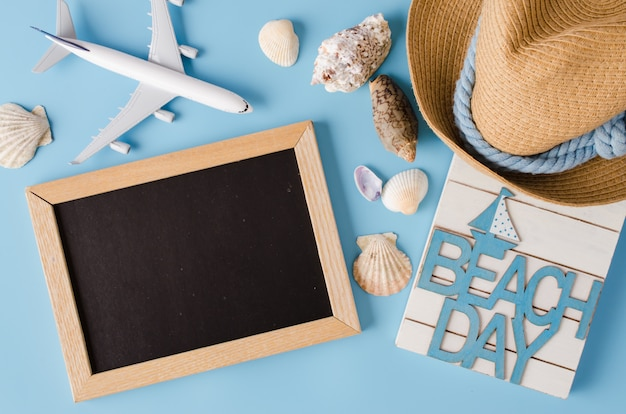 Empty chalkboard with seashells and decorative airplane. summer travel concept.