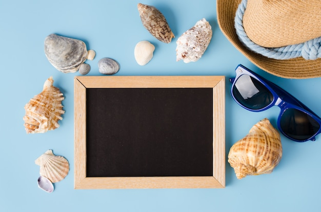 Empty chalkboard with seashells, hat and glasses.