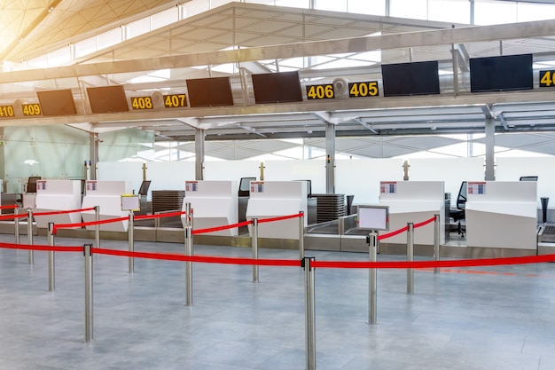 Empty check-in desks for drop off baggage with paths canceled with a red ribbon to differentiate passengers at the airport terminal.