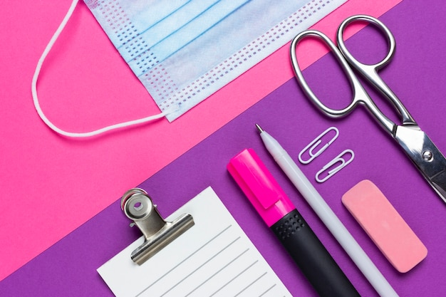 An empty checklist lies next to a medical mask, scissors, notebook, pen, eraser, paper clip and marker on a pink and purple background. office work during the epidemic