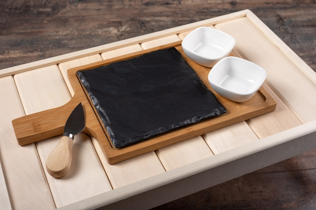 Пустая доска подачи сыра на деревянной деревенской предпосылке. пустой деревянный поднос для завтрака