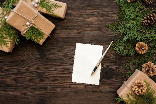 Empty christmas card, gifts boxes, branch and fir cones on wood