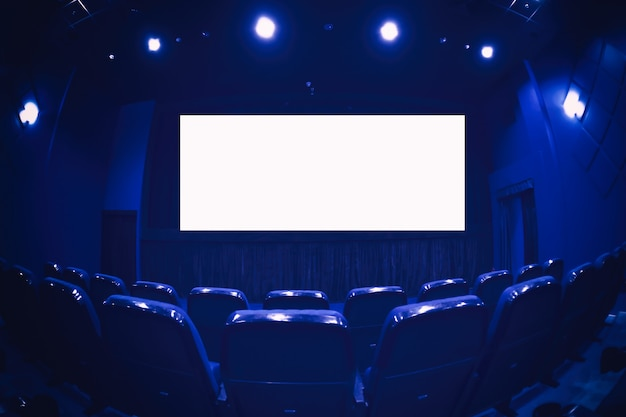 Empty cinema auditorium with empty white screen. empty rows of theater or movie seats.