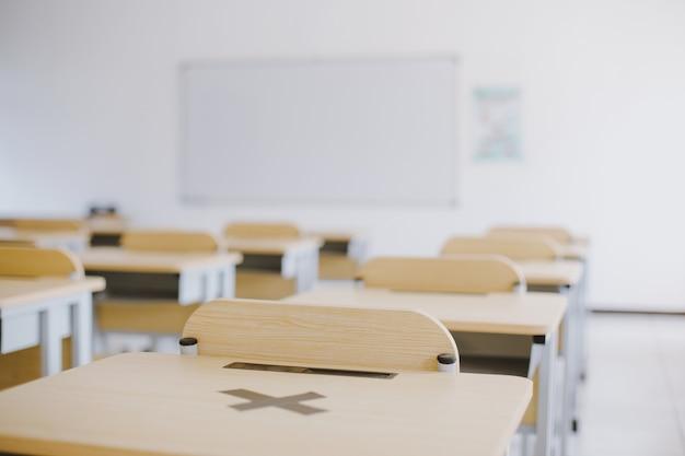 Пустой класс без ученика с партами, стульями и доской во время пандемии
