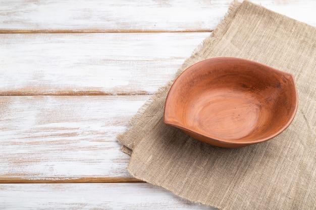흰색 나무 배경 및 리넨 섬유에 빈 점토 갈색 그릇. 측면보기, 닫기, 복사 공간.