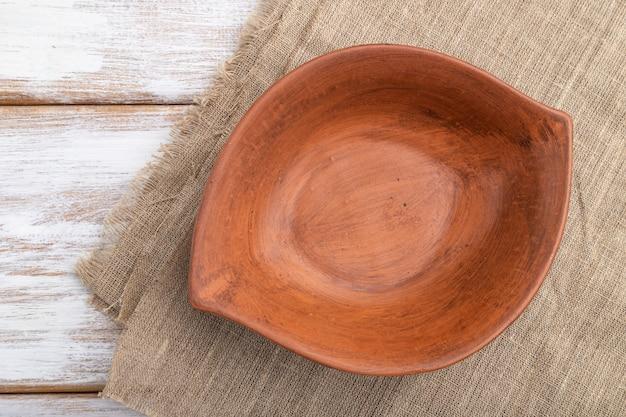 흰색 나무 배경 및 리넨 섬유에 빈 점토 갈색 그릇. 평면도, 클로즈업, 평평하다.