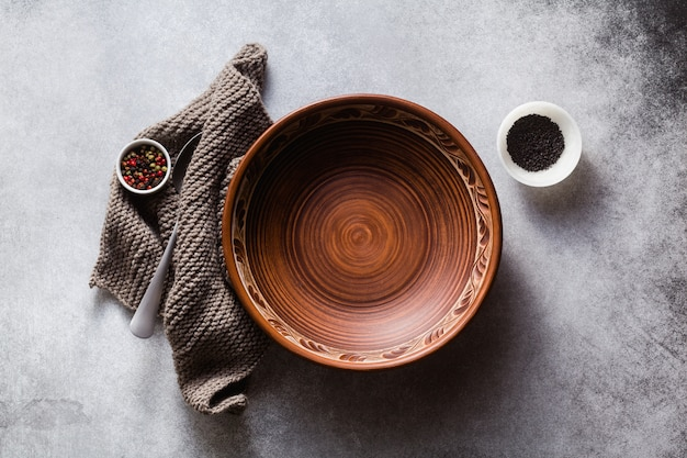 Empty clay plates on the table set for lunch or dinner.