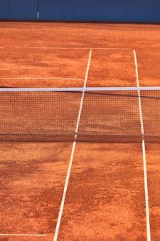 빈 클레이 테니스 코트와 그물. 세로 샷