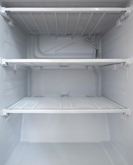 Вылейте чистую морозильную камеру в холодильник. пустые полки в холодильнике.