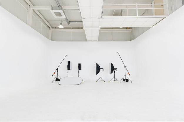 Пустой чистый никто в комнате мастерской фотостудии, полный профессионального фотографического оборудования, софтбокс, стробоскоп, отражатель, штатив, лампочки, аккуратно размещают на белом фоне пола и стены.