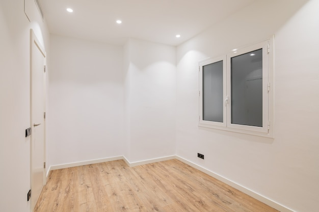 Empty clean room after renovation with white walls window and wooden floor
