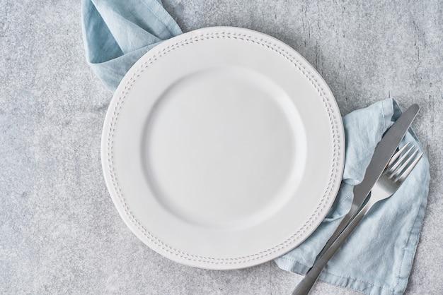 Пустая чистая белая круглая тарелка на серой льняной скатерти с серебряными изделиями