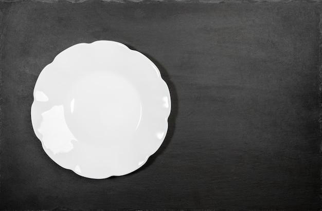 셰일 서빙 보드의 검은 배경에 생각 된 물결 모양 가장자리와 빈 깨끗 한 흰색 접시. 준비된 요리를 모의하십시오. 레시피 또는 텍스트를위한 공간을 복사합니다. 오버 헤드보기. 최소한의 이미지.