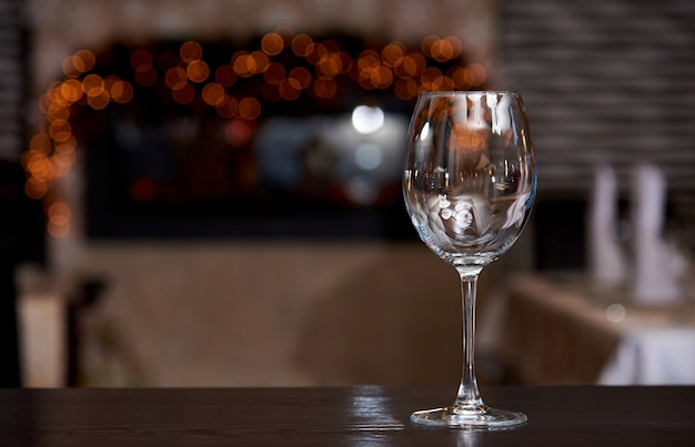 Empty clean wine glass with reflection on a blurred background with bokeh.