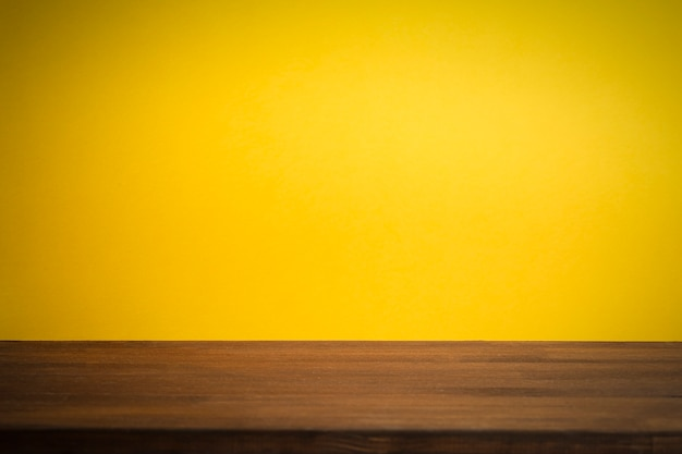 Empty clean yellow background with wooden table.