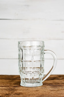 Empty clear beer glass, mug on wooden table. vertical, copy space