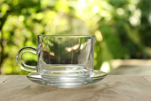 Empty clear glass of tea on bokeh green leaf background.
