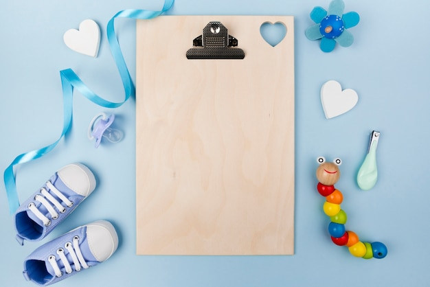 Empty clipboard and baby shoes
