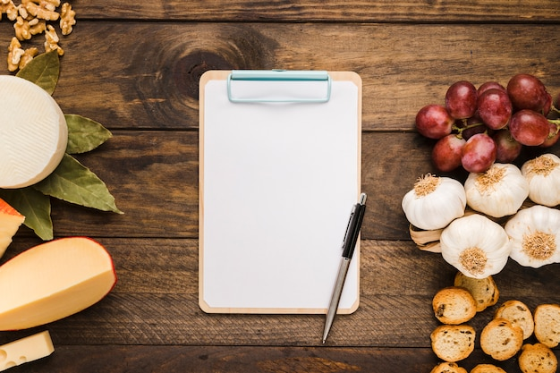 Empty clipboard and fresh ingredient on wooden desk