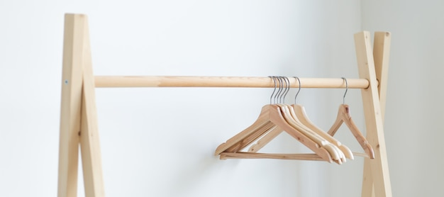 Empty clothes hangers hanging on a clothes rack in the bedroom. copy spase