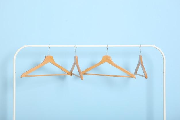 Пустые вешалки для одежды на шкафу на цветном фоне