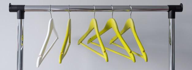 Пустые вешалки на металлическом рельсе на сером