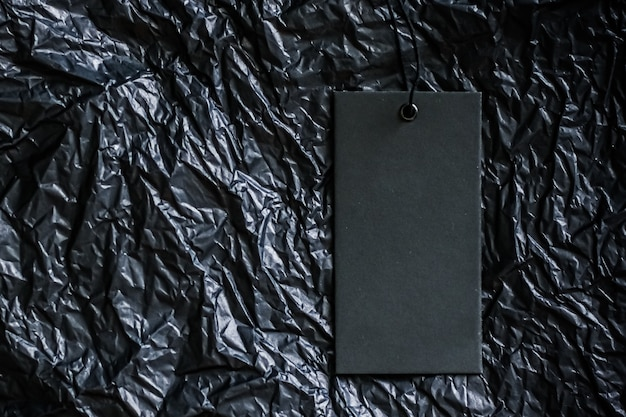 Пустая бирка одежды на черном фоне с концепцией устойчивой моды и бренда copyspace