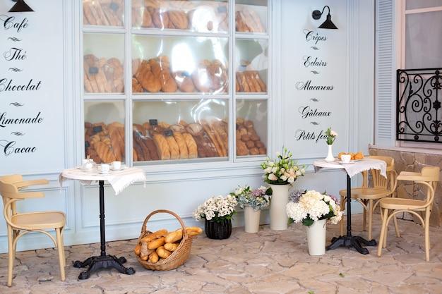 空のコーヒーとフランス風のテーブルと椅子のあるレストランのテラス。パン屋のディスプレイケースに焼きたてのペストリー、パン、パン。ストリートカフェの装飾、インテリアのコンセプト。装飾ベーカリー。
