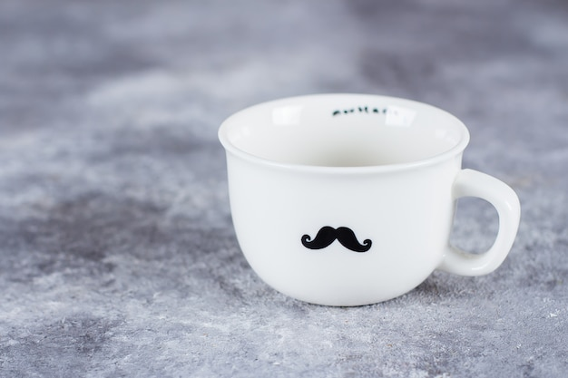 Empty coffee cup on grey stone concrete table background with mustache drawing.
