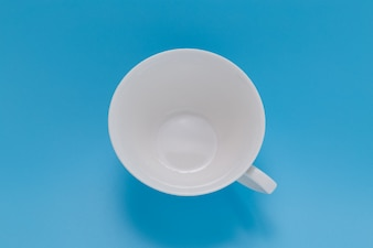 Empty coffee cup top view on blue background.