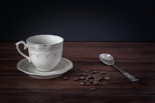접시에 빈 커피 잔, 어두운 테이블 보드에 실버 스푼으로 커피 콩
