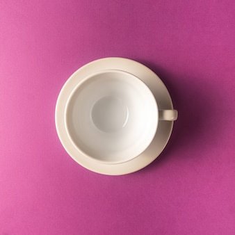 Empty coffee or tea cup on purple color background, copy space.