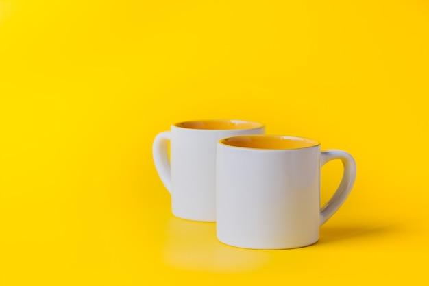 黄色の背景に黄色の空のコーヒーまたは紅茶の白いカップ。テキスト用のスペースをコピーします。