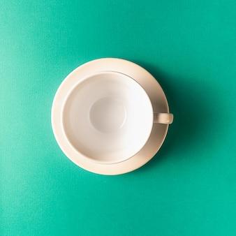 Empty coffee or tea cup on aqua color background, copy space.