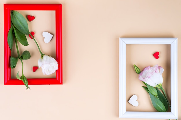 Empty color frames, red hearts and flowers eustoma on beige surface with copy space.