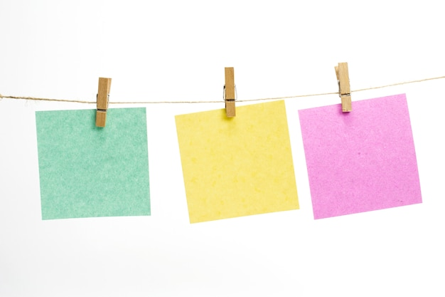 Empty colored paper sheets for notes, frames that hang on a rope with clothespins and isolated on white.