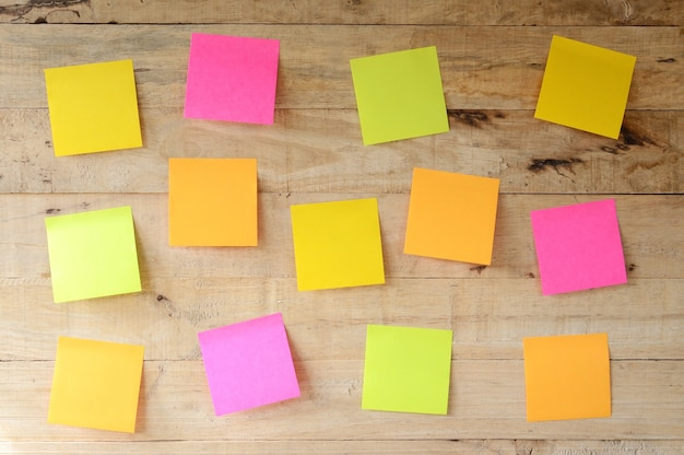 Empty colorful sticky notes on wooden bulletin board