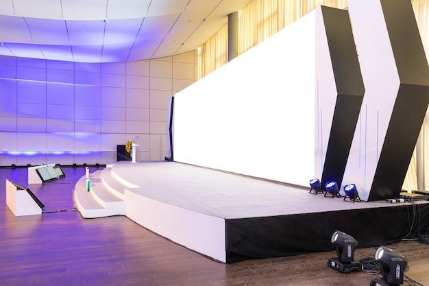 Empty conference hall with empty white projector screen