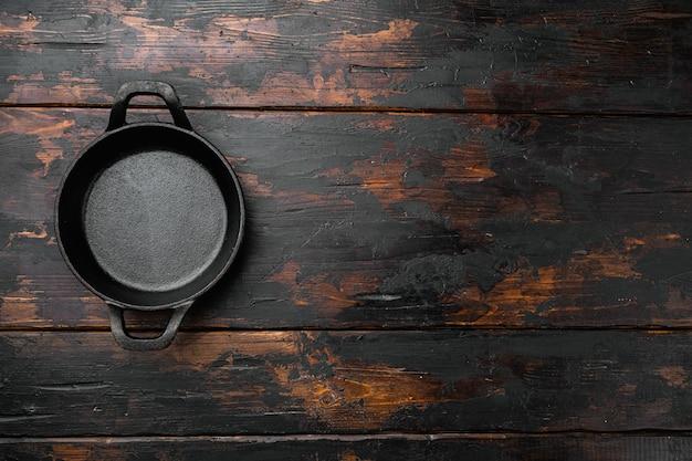 텍스트나 음식을 위한 복사 공간이 있는 빈 요리 냄비 세트, 오래된 어두운 나무 테이블 배경 위에 있는 평면도