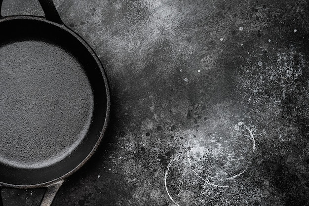 Empty cooking pot set with copy space for text or food with copy space for text or food, top view flat lay, on black dark stone table background