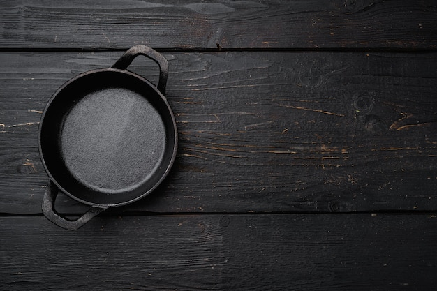 Empty cooking pot set with copy space for text or food with copy space for text or food, top view flat lay, on black wooden table background