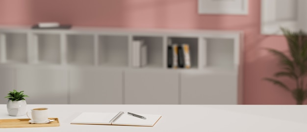 Empty copy space on white table with book pen coffee mug and tree pot pink office interior