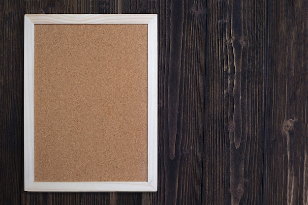 Empty cork board with wooden frame on wooden desk