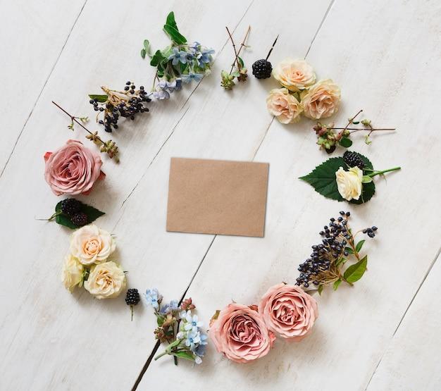 生花とドライフラワーの輪の空のクラフト紙グリーティングカード