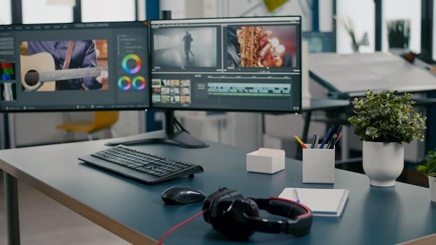 机の上に置かれたプロのコンピューターを備えた空のクリエイティブマルチメディアスタジオデュアルモニターセットアップビデオ..。