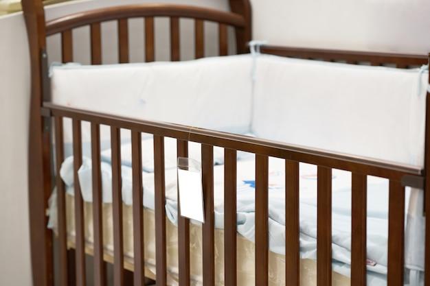 枕とプライススリップラベルのあるベビーベッド