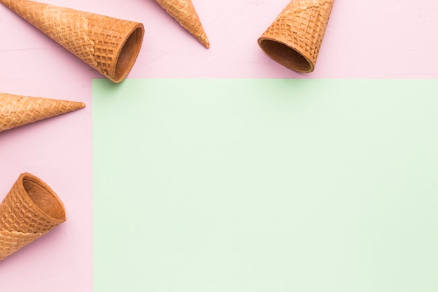 Empty crispy ice cream cones on multicolored surface