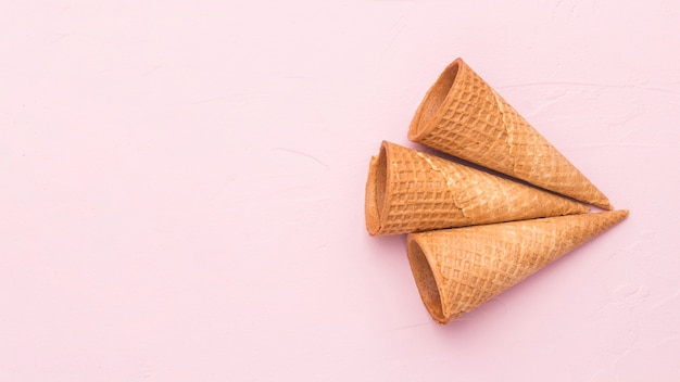 Empty crispy waffle ice cream cones on pink surface